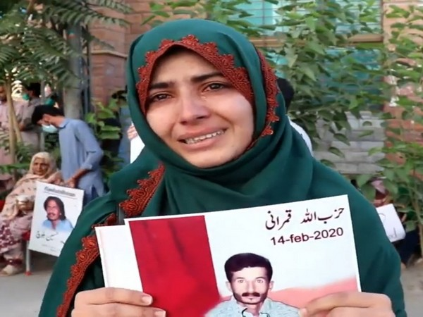 A Baloch woman holds the photo of her missing family member.