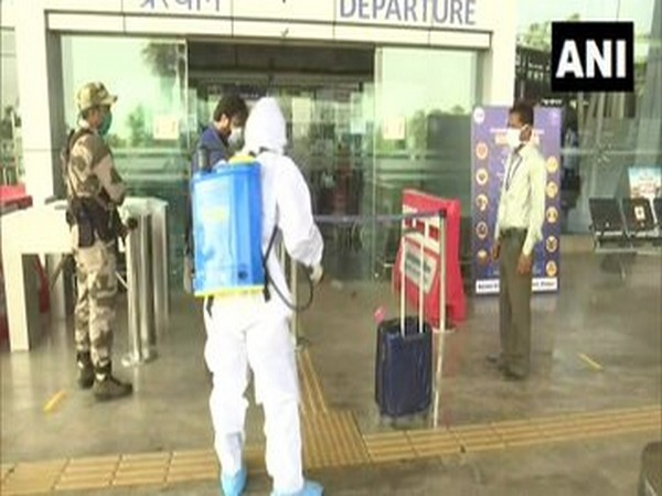 Airport staff disinfects luggage of passengers arriving at Swami Vivekananda Airport in Raipur on Monday. [Photo/ANI]
