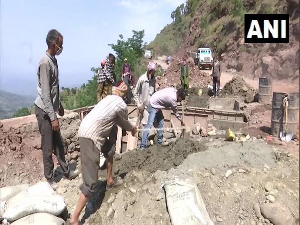 Locals of Drajj village working of a community development project on Monday. Photo/ANI
