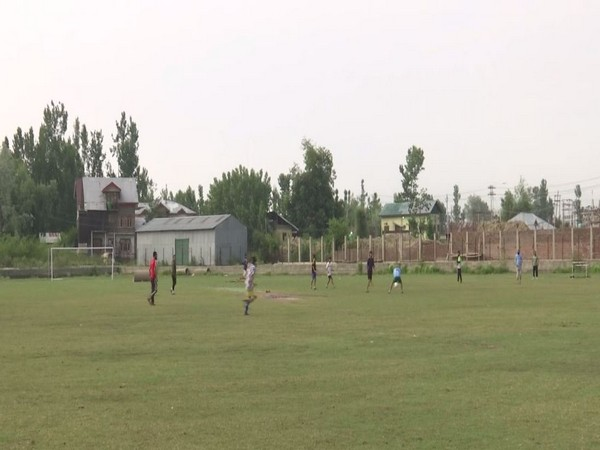 Locals playing football in the playground in Srinagar. (Photo/ANI)