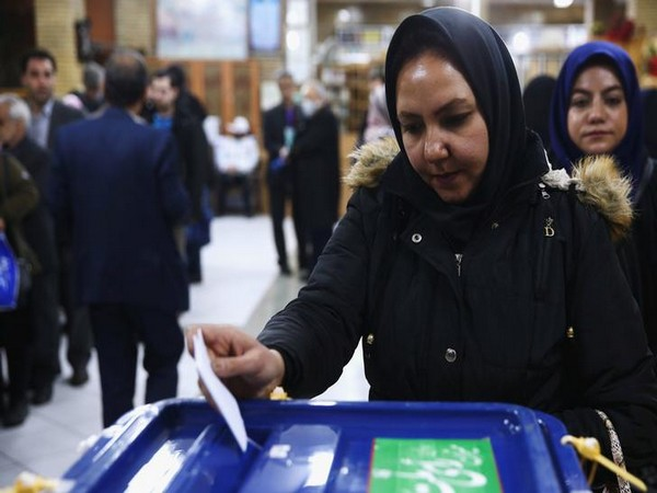An Iranian woman casts her vote during parliamentary elections at a polling station in Tehran