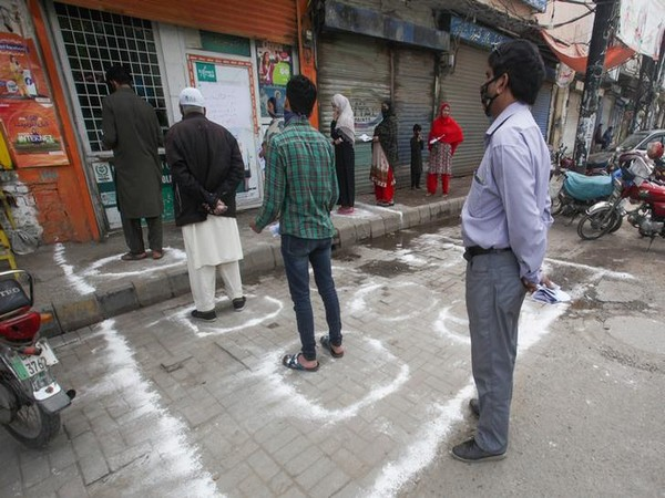 People stand in circles drawn with chalk to maintain safe distance outside a bank, during a lockdown