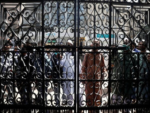 People stand outside the locked entrance gate of a mosque as they arrive to attend Friday prayer despite a lockdown
