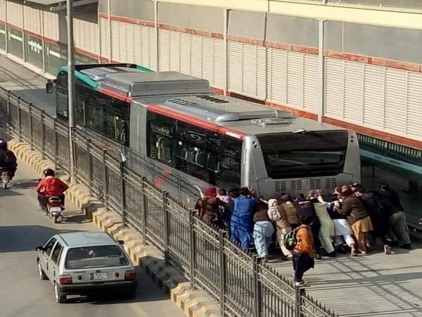 Passengers pushing the BRT bus that broke down in Peshawar.