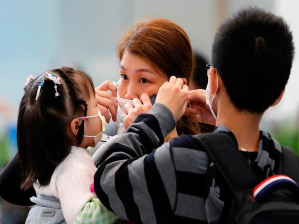 A woman adjusts her mask to prevent an outbreak of a new coronavirus