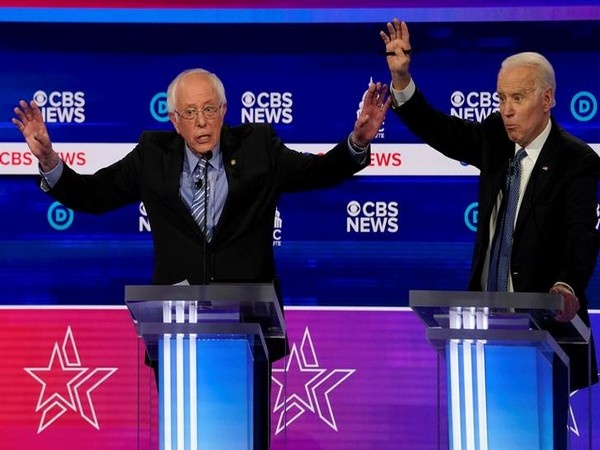 Democratic candidates Senator Bernie Sanders and former Vice President Joe Biden brush hands during the Democratic 2020 presidential debate in South Carolina.