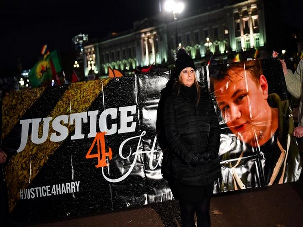Harry Dunn's mother Charlotte Charles poses in front of a banner outside the Buckingham Palace as people demonstrate during U.S