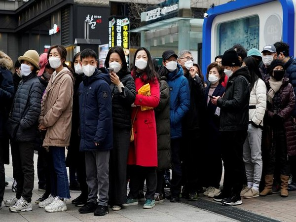 People wearing masks after the coronavirus outbreak wait in a line to buy masks in front of a department store in Seoul