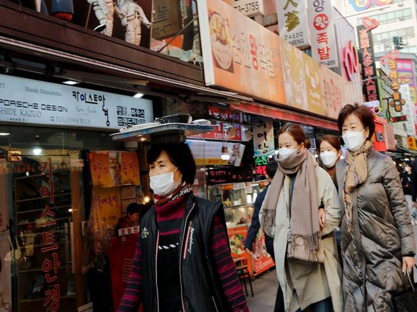 Women wearing masks as a preventive measure against the coronavirus walk at a traditional market in Seoul