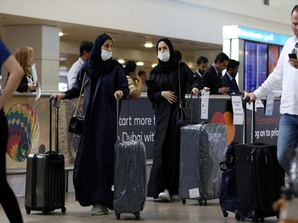 Travellers wear masks as they arrive at the Dubai International Airport in UAE.