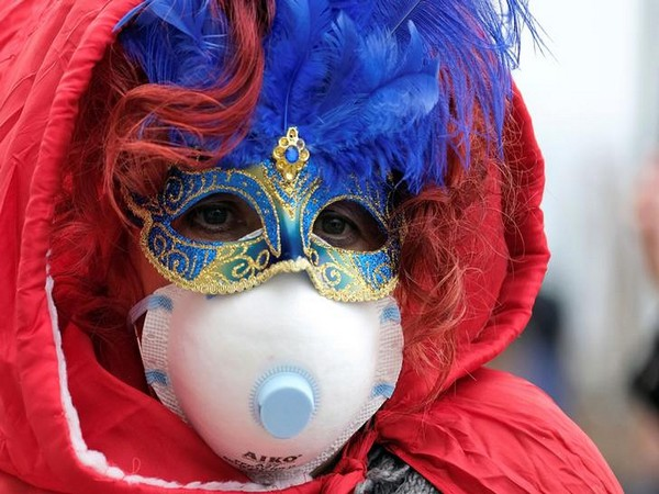Masked Carnival reveler wearing a protective face mask at Venice Carnival, amid outbreak coronavirus, in Venice, Italy.