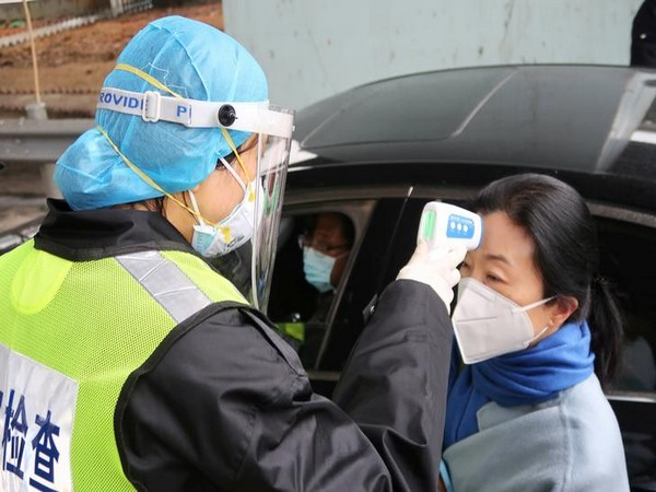 A security officer in a protective mask checks the temperature of a passenger following the outbreak of a new coronavirus in Xianning, China.