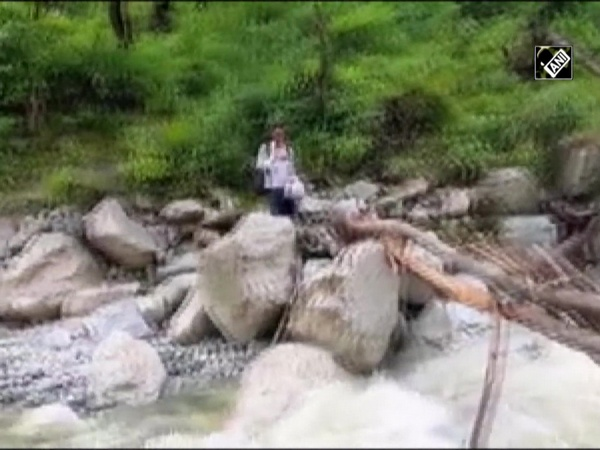 People using makeshift wooden bridge to cross river stream in Uttarkashi