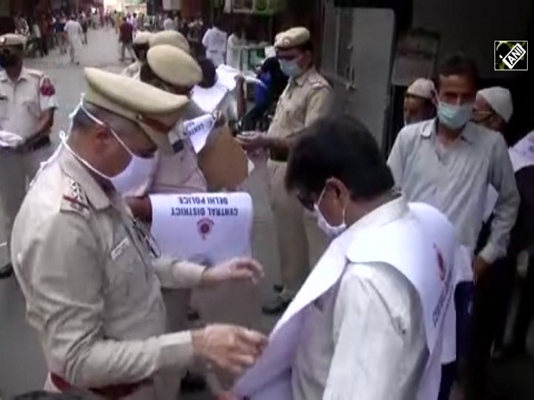 Delhi Police distribute 'Keep a distance of two gaz' paper jackets in Jama Masjid area